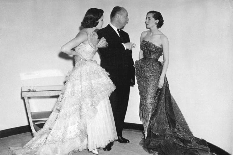 Christian Dior (tengah) bersama dua model yang mengenakan busana rancangannya pada 24 April 1950. (AFP/Pigiste)