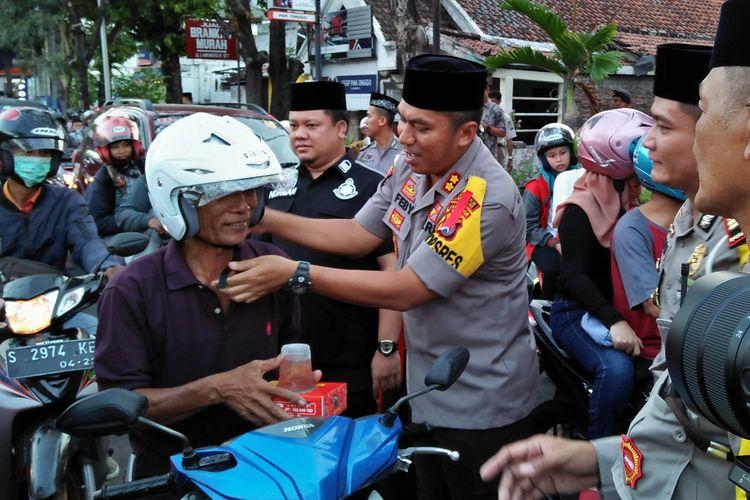 Kapolres Lamongan AKBP Feby DP Hutagalung didampingi Kasat Lantas Polres Lamongan AKP Argya Satrya Bhawana, saat membagikan takjil dan helm gratis kepada pengendara sepeda motor.