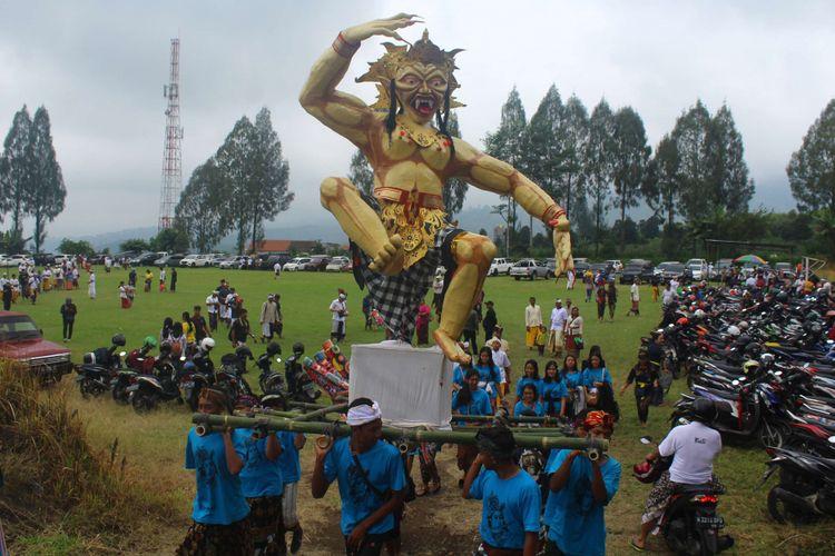 Sejumlah umat Hindu mengarak ogoh-ogoh sebelum membakarnya pada Upacara Tawur Agung Kesanga di Lapangan Junggo, Kecamatan Bumiaji, Kota Batu, Jawa Timur, Rabu (6/3/2019). Upacara tersebut merupakan rangkaian Perayaan Hari Raya Nyepi Saka Warsa 1941.