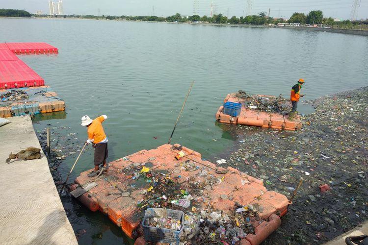 Petugas kebersihan membersihkan permukaan waduk Cincin, Papanggo, Jakarta Utara dari sampah, Minggu (10/12/2017)