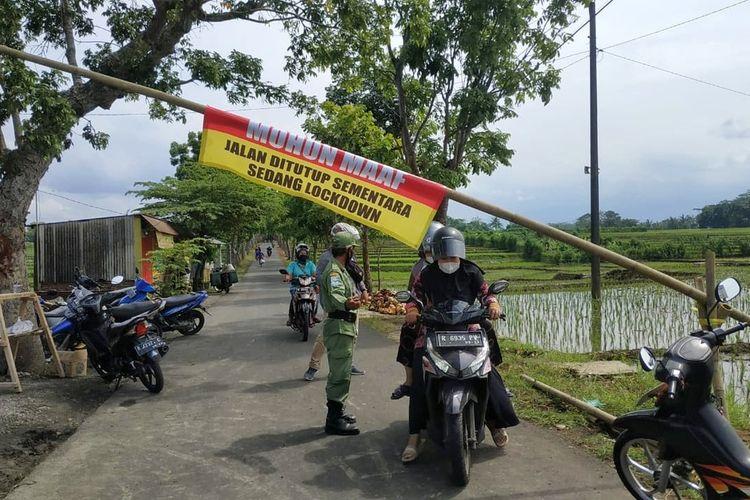 Satuan tugas Covid-19 Desa Manduraga, Kecamatan Kalimanah, Purbalingga, Jawa Tengah berjaga di jalan masuk desa setelah 20 warganya terkonfirmasi positif Covid-19, Jumat (18/6/2021).