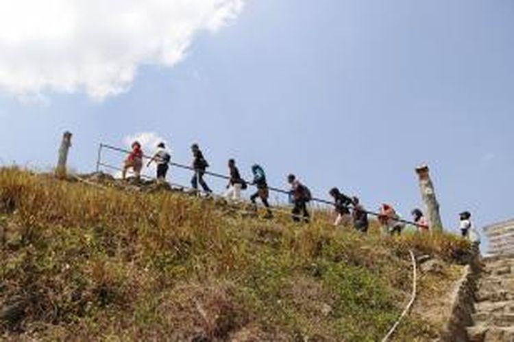 Para wisatawan menaiki anak tangga menuju Embung Nglanggeran yang berlokasi di Desa Nglanggeran, Patuk, Gunung Kidul, Yogyakarta, Minggu (23/8/2015). Wisatawan harus menaiki anak tangga selama hampir 10 waktu ntuk dapat mencapai Embung Nglanggeran.