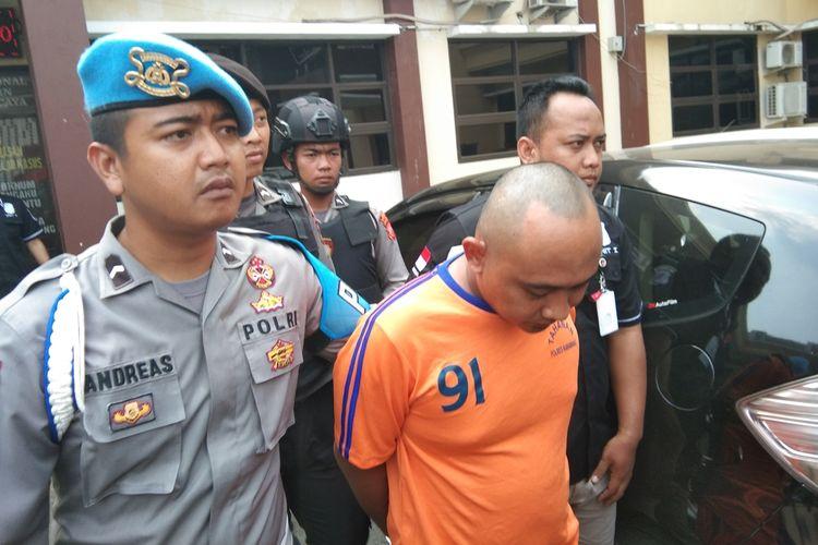 Ridwan Solihin (baju orange), pelaku pembunuhan wanita yang ditemukan tewas dalam kamar Hotel Omega, Karawang saat digiring polisi usai press release kasus tersebut di Mapolres Karawang, Selasa (15/10/2019).