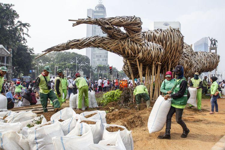Petugas Suku Dinas Kehutanan Jakarta Pusat mengganti tanaman yang rusak di sekitar instalasi bambu Getah Getih, Jakarta, Minggu (23/6/2019). Perbaikan tersebut dilakukan karena tanaman hias di kawasan tersebut rusak akibat terinjak warga saat menghadiri perayaan HUT Jakarta ke-492, Sabtu (22/6/2019).
