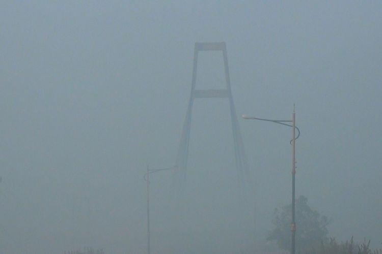 Jembatan Pesona Tanjung Senai yang merupakan icon Ogan Ilir terlihat samar tertutup kabut asap sisa kebakaran lahan di Ogan Ilir dan Ogan Komering Ilir, Jumat (13/9/2019).