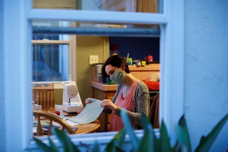 warga AS Jillian Kislow membuat masker wajah untuk teman-temannya di dapurnya selama wabah global penyakit coronavirus (COVID-19) di Pasadena, California, AS, 26 Maret 2020.