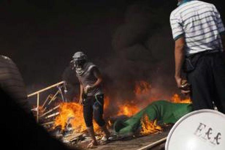 Pendukung Presiden Mesir terguling Muhammad Mursi melewati barikade api membawa bom bensin selama bentrokan melawan pasukan keamanan di Kota Nasr, Mesir, 14 Agustus 2013.