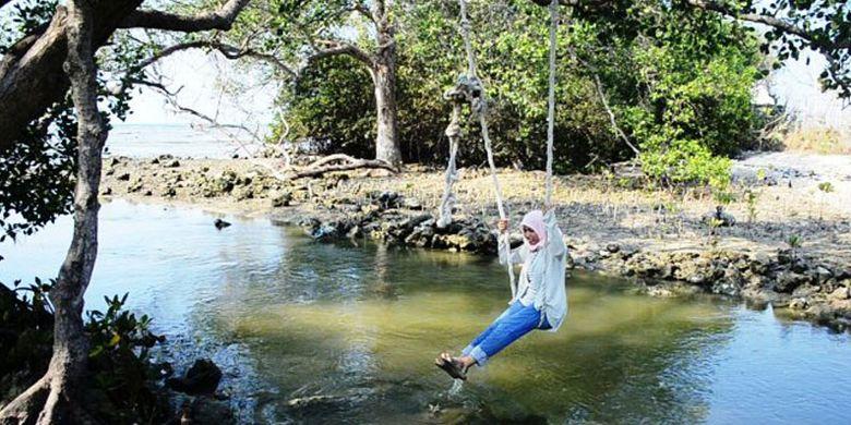 Seorang pengunjung bermain ayunan di Pantau Kutang, Lamongan, Jawa Timur.