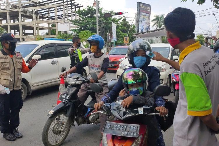 Petugas memeriksa suhu tubuh pengendara yang melintas di Pos Chek Point di Jalan Sultan Agung Kota Tegal, saat penerapan isolasi wilayah menjelang PSBB, Selasa (21/4/2020)