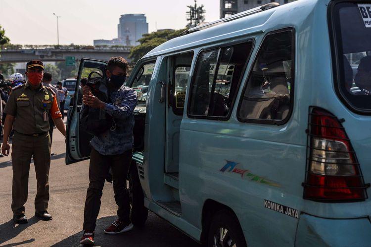 Petugas gabungan dalam Operasi Yustisi Protokol COVID-19 menggelar razia angkutan umum yang melanggar batas kapasitas angkutan orang di Kawasan Tanah Abang, Jakarta Pusat, Senin (21/9/2020). Operasi Yustisi tersebut dilaksanakan untuk menertibkan masyarakat agar lebih disiplin dalam menerapkan protokol kesehatan pencegahan penyebaran Covid-19.