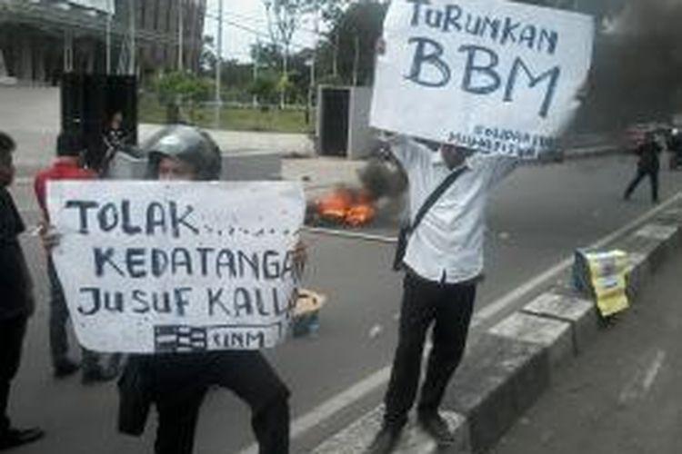 Mahasiswa Universitas Negeri Makassar (UNM) melakukan aksi menolak kedatangan Wakil Presiden (Wapres) Jusuf Kalla) dan membakar ban bekas di  badan jalan AP Pettarani, depan gedung Phinisi Makassar, Senin (6/4/2015).