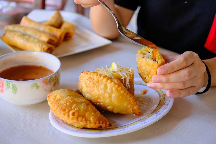 Ilustrasi jalangkote disiram saus cabai khas. Jalangkote adalah kuliner khas Makassar yang bentuknya mirip pastel.