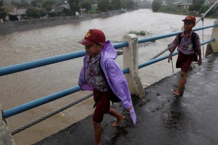 Warga melintas Bendungan Katulampa, Bogor, Jawa Barat, saat hujan lebat mengguyur Bogor, Rabu (9/1/2013). Ketinggian air di Bendungan Katulampa mencapai 120 sentimeter melebihi batas normal yaitu 50 sentimeter sehingga ditetapkan status siaga tiga. Warga terutama yang tinggal di daerah bantaran-bantaran sungai dihimbau bersiaga dan mengantisipasi datangnya banjir. KOMPAS IMAGES/KRISTIANTO PURNOMO