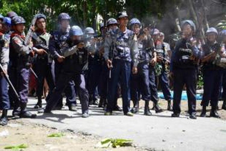 Foto yang dirilis oleh Human Rights Watch (HRW), 22 April 2013 menunjukkan seorang polisi mengarahkan senjata mesin selama kerusuhan etnis di Sittwe, Rakhine, Myanmar, Juni 2012.