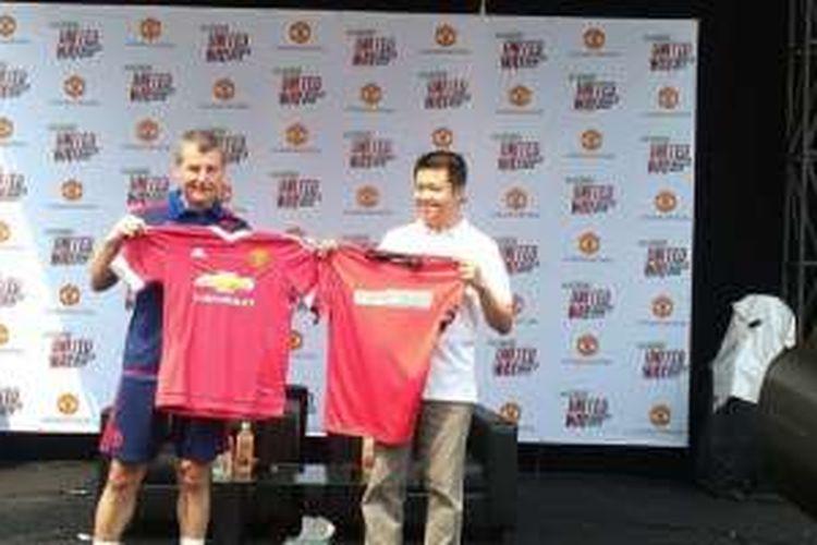 Legenda Manchester United, Denis Irwin (kiri), bertukar kostum dengan Sales and Marketing Manager You-C 1000 Isotonic Drink, Henky Prabowo, di GOR Soemantri, Kuningan, Jakarta (7/5).