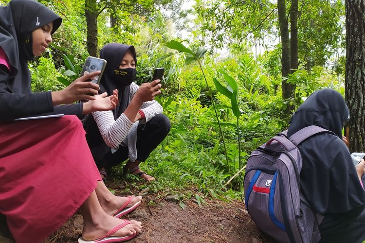 Siswa MTs Pakis mengerjakan ujian tengah semester (UTS) secara daring di bukit Dusun Pesawahan Desa Gununglurah, Kecamatan Cilongok, Kabupaten Banyumas, Jawa Tengah, Selasa (22/9/2020).