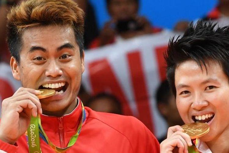 Pasangan ganda campuran Indonesia Tontowi Ahmad (kiri) dan Liliyana Natsir melakukan tradisi gigit medali emas. Mereka adalah peraih medali emas pertama untuk Indonesia pada Olimpiade 2016.