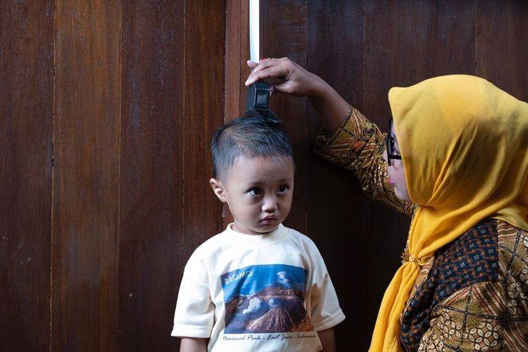 Petugas kesehatan sedang mengukur tinggi badan seorang anak