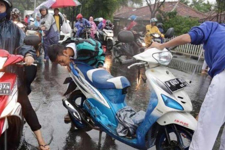 Sejumlah sepeda motor mogok saat melewati banjir di Jalan Budi Jaya, Kebun Jeruk, Jakarta, Senin (9/2/2015). Curah hujan yang tinggi mengakibatkan sejumlah tempat di ibu kota terendam banjir.