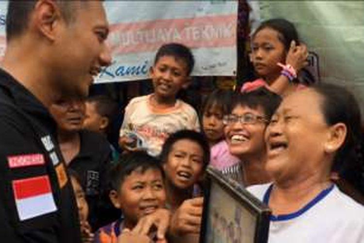 Seorang ibu tampak semringah saat calon gubernur DKI Jakarta, Agus Harimurti Yudhoyono, berkunjung ke kawasan rumahnya di Pademangan, Jakarta Utara, Senin (14/11/2016).   Dengan kaos demokrat, ibu itu menunjukkan foto dia sekeluarga dengan mantan Presiden RI Ke-6 Susilo Bambang Yudhoyono (SBY) ke Agus.