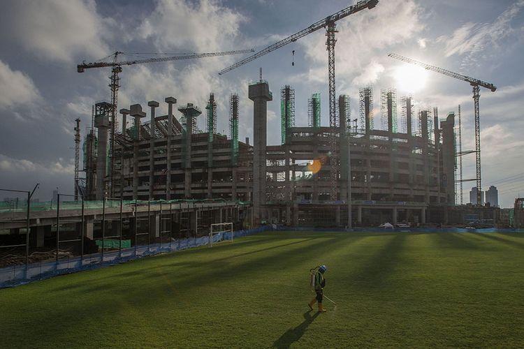 Pekerja merawat rumput lapangan latihan di lokasi pembangunan Jakarta International Stadium (JIS) di Papanggo, Tanjung Priok, Jakarta Utara, Selasa (9/3/2021). Saat ini kemajuan pembangunan stadion yang diproyeksikan berkapasitas 82.000 penonton itu mencapai 49,94 persen (data terakhir PT Jakarta Propertindo per 9 Maret 2021).