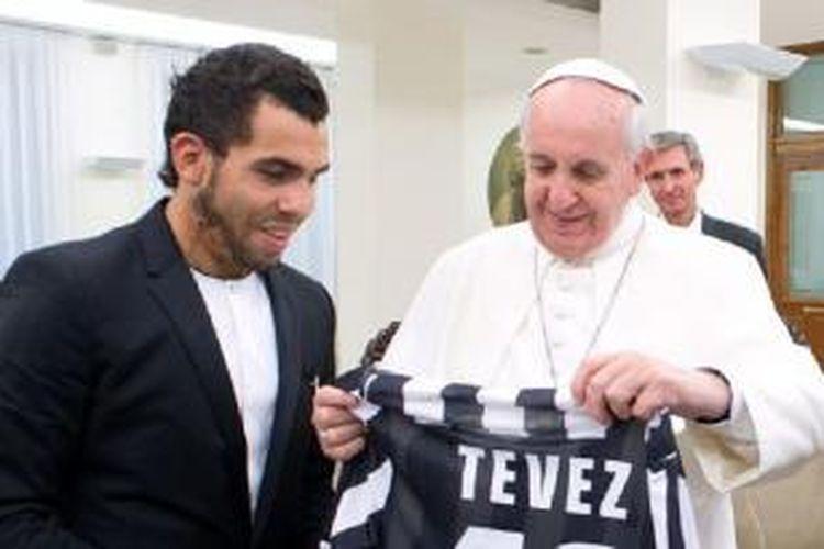 Penyerang Juventus, Carlos Tevez, saat menemui Paus Fransiskus di Basilika Santo Petrus, Vatikan. Pertemuan keduanya untuk membahas masalah kemiskinan yang terjadi di ibu kota Argentina, Buenos Aires.