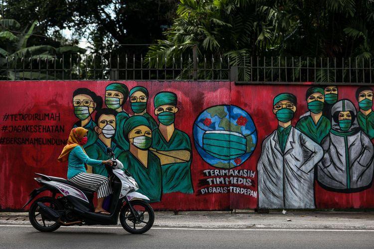 Warga menggunakan masker saat mengendarai sepeda motor melintas di depan mural tentang pandemi virus corona atau COVID-19 di Jalan Raya Jakarta-Bogor, Depok, Jawa Barat, Selasa (7/4/2020). Mural tersebut ditujukan sebagai bentuk dukungan kepada tenaga medis yang menjadi garda terdepan dalam menghadapi COVID-19 di Indonesia.