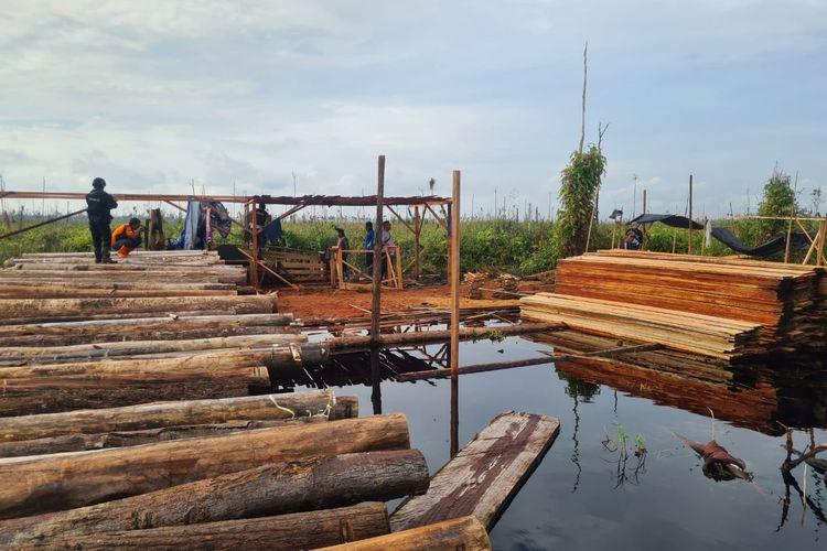 Pengamanan kayu hasil pembalakan liar di lokasi PT Pesona Belantara Persada di Desa Betung,  Muarojambi, oleh kepolisian saat operasi udara memantau karhutla.
