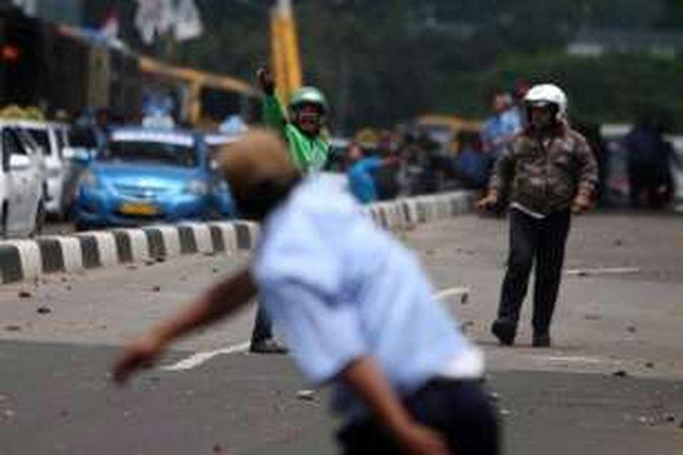 Sopir taksi dan pengemudi ojek berbasis aplikasi online saling lempar batu saat bentrok di Jalan Jenderal Sudirman, Karet, Jakarta, Selasa (22/3/2015). Sopir taksi berunjuk rasa menolak beroperasinya angkutan berbasis aplikasi online.