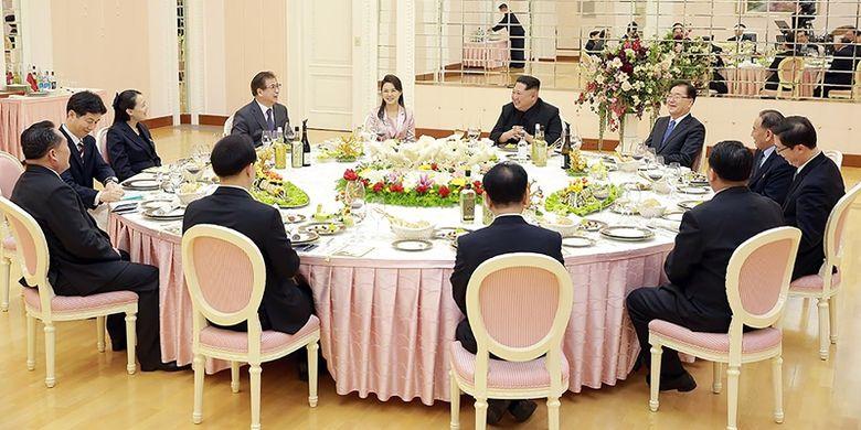 Pemimpin Korea Utara Kim Jong Un (kanan tengah) berbicara dengan delegasi Korea Selatan saat makan malam di Pyongyang, Korea Utara, Senin (5/3/2018). (KCNA via AFP)
