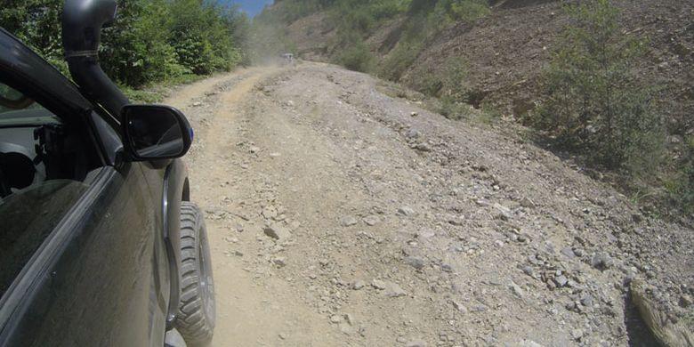 Mobil penggerak empat roda melewati jalan yang rusak di Pegunungan Arfak, Papua Barat, Kamis (16/8/2018). Akses jalan rusak menuju Pegunungan Arfak dari Manokwari adalah tantangan untuk pengembangan pariwisata Pegunungan Arfak.