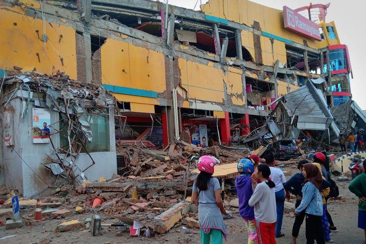 Warga melihat bangunan pusat perbelanjaan yang ambruk akibat gempa di Palu, Sulawesi Tengah, Sabtu (29/9/2018).
