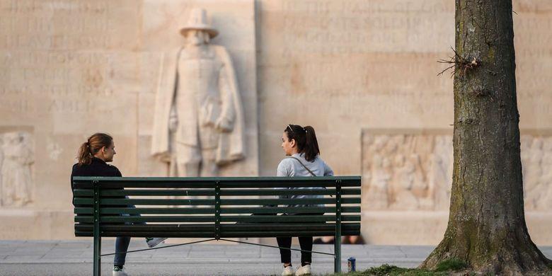 Dua orang wanita menjaga jarak sosial saat mengobrol di kursi taman di Jenewa, Swiss, 18 Maret 2020. Menjaga jarak aman antar warga merupakan salah satu cara yang dianjurkan untuk mencegah penyebaran virus corona.