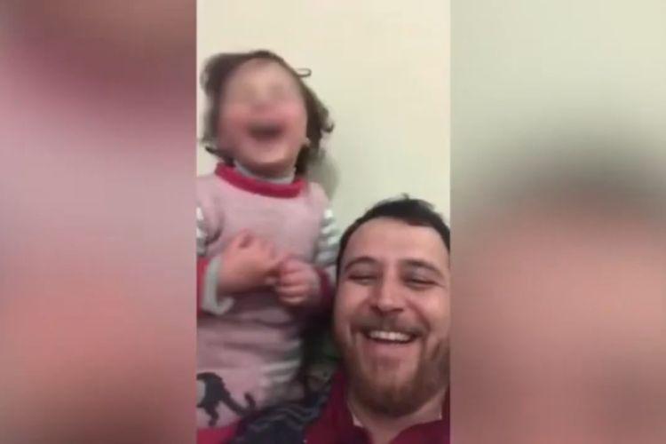 Abdullah al-Mohammad tertawa bersama anaknya, Salwa, di mana bocah tiga tahun tersebut diajari untuk tetap gembira di tengah suara bom yang menggelegar.