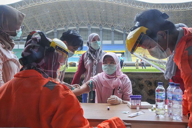 Petugas medis mengecek kesehatannya dengan mengambil sampel  darah dengan metode rapid test (pemeriksaan cepat) di Stadion Patriot Candrabhaga, Bekasi, Jawa Barat, Rabu (25/3/2020). Pemeriksaan yang dilakukan khusus tenaga medis di Bekasi guna memutus mata rantai penyebaran virus COVID-19.