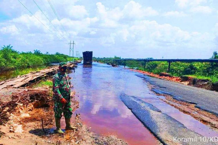 Babinsa Koramil 10/Kunto Darussalam mendatangi lokasi jalan lintas Rohul-Bengkalis rusak yang terendam air di Desa Bonai, Kecamatan Bonai Darussalam, Kabupaten Rohul, Riau, Minggu (31/1/2021).