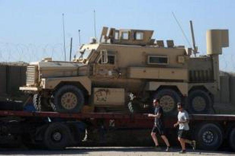 Dua prajurit AS sedang berjoging melintasi sebuah kendaraan penyapu ranjau yang dimuat di atas sebuah truk yang akan membawanya keluar dari Provinsi Ghazni, Afganistan sebagai bagian penarikan mundur pasukan AS dari negeri itu.