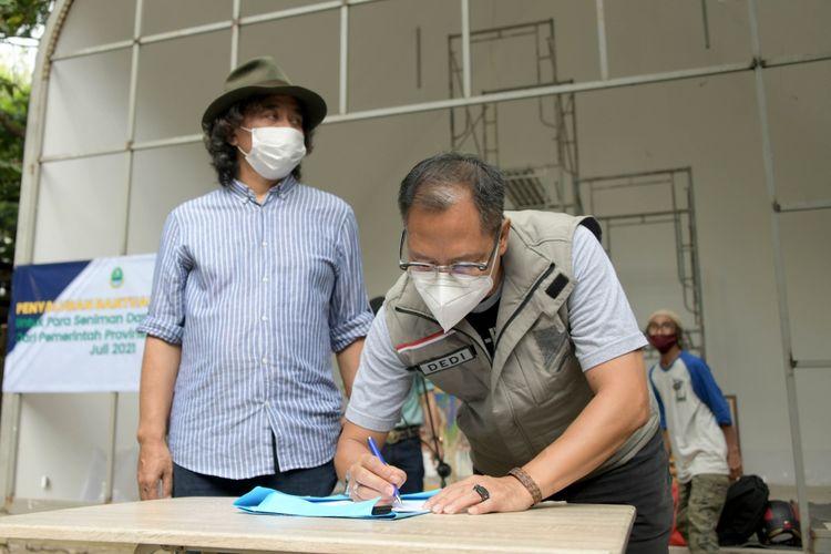 Pemda Provinsi Jabar saat menyalurkan bantuan sosial (bansos) berupa sembako dan uang tunai Rp400 ribu kepada seniman dan budayawan yang terdampak Pemberlakuan Pembatasan Kegiatan Masyarakat (PPKM) di Sanggar Olah Seni, Babakan Siliwangi, Kota Bandung, Jumat (23/7/2021).