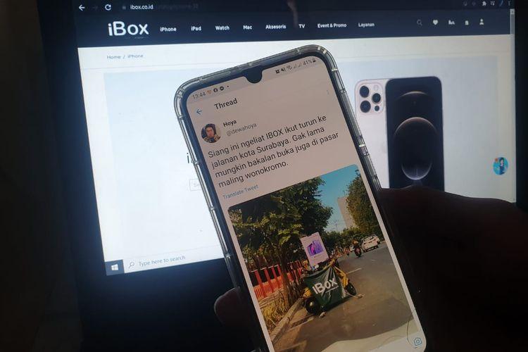 Pengguna Twitter dengan handle @dewahoya, mengunggah foto spanduk iBox dan iPhone 12 yang terpajang di tepi jalan di daerah Surabaya.