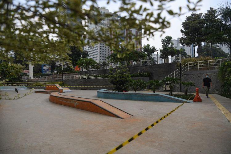 Seorang warga melintasi tali pembatas yang dipasang  di area Skate Park kawasan Dukuh Atas, Jakarta, Minggu (27/6/2021). Pembatasan kegiatan oleh pemerintah melalui PPKM Mikro hingga 5 Juli 2021 antara lain penutupan ruang publik, pembatasan operasional transportasi serta  penerapan protokol lebih ketat diharapkan dapat mengurangi penyebaran COVID-19 dimana fasilitas kesehatan telah penuh dalam menghadapi lonjakan pasien terkonfirmasi COVID-19. ANTARA FOTO/Wahyu Putro A/aww.