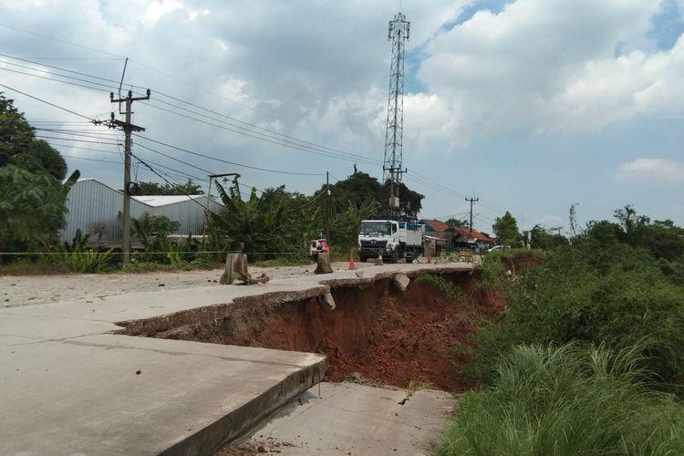 Sebuah kendaraan melewati jalan inspeksi Tamelang-Curug, Karawang yang amblas hampir separuh badan jalan, Kamis (11/2/2021).