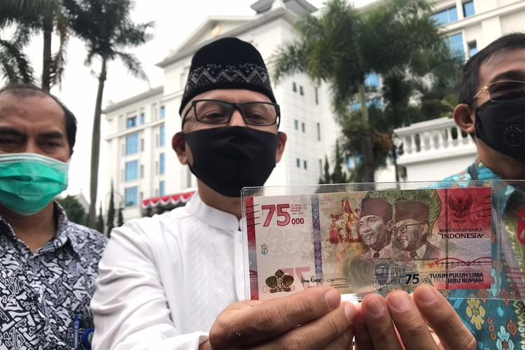 Kepala Kantor Perwakilan Bank Indonesia Provinsi Jabar, Herawanto  memperlihatkan uang pecahan baru Rp 75.000. Masyarakat mulai bisa menukar uang tersebut hari ini.