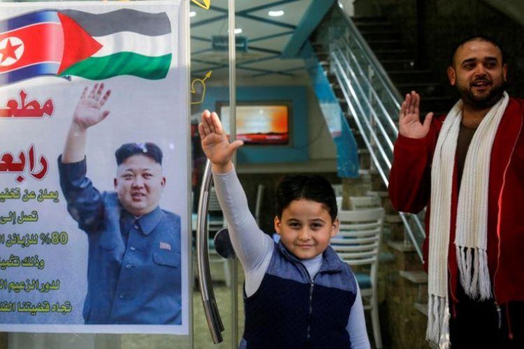 Salim Rabaa (kanan) berdiri di depan restorannya di Jalur Gaza yang dihiasi poster berisi ucapan terima kasih untuk Kim Jong Un.