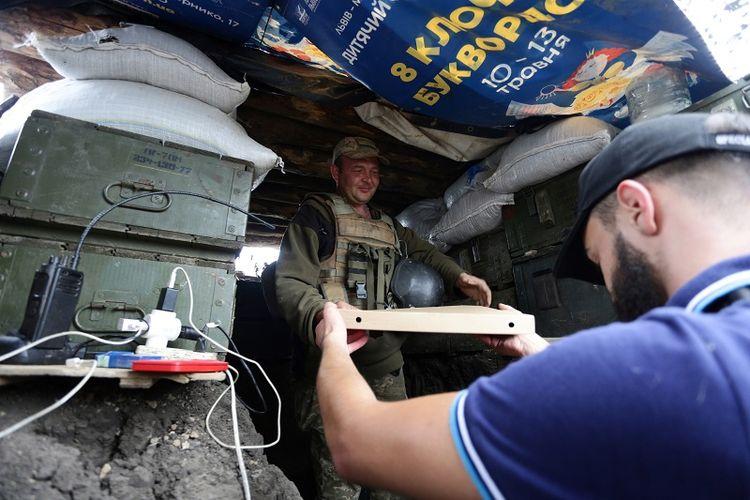 Aleksey Kachko, salah seorang pemilik kedai Pizza Veterano in Mariupol, Ukraina menyerahkan sekotak pizza kepada seorang tentara Ukraina yang bertugas di garis depan menghadapi pemberontak pro-Rusia di wilayah timur negeri itu.