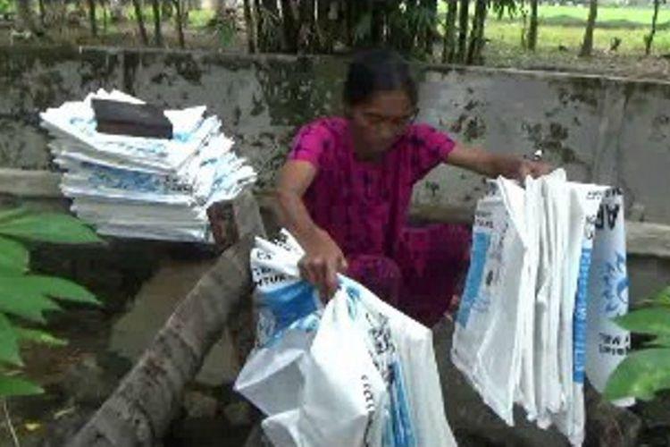 Sitti Nur (45 tahun), janda asal Desa Rea, Kecamatan Binuang, Polewali Mandar tenga menyuci karung bekas. Satu karung dihargai Rp 50.