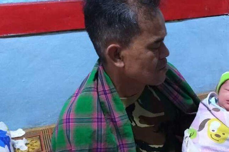 Mahmudin (55), ayah kandung seorang perempuan yang melahirkan anak ketiganya dengan kandungan hanya 1 jam sedang mengendong cucunya, Selasa (21/7/2020).(KOMPAS.COM/IRWAN NUGRAHA)