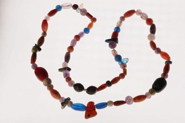 Salah satu kalung memiliki panjang 70 sentimeter, dibuat dari manik-manik berwarna gelap dan biru.