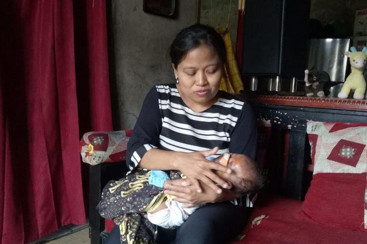 Lisdawati (40) ibunda AP sedang merawat bayi perempuannya setelah diperbolehkan pulang dari rumah sakit oleh dokter, Sabtu (23/11/2019).