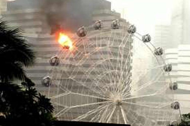 Komidi putar raksasa di sebuah tempat hiburan yang baru dibuka di Bangkok, Thailand, terbakar di tengah terpaan badai.