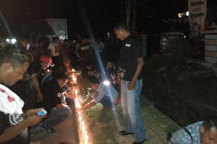 Para relawan Jokowi, sedang menyalakan lilin di depan Kantor KPU NTT, Minggu (21/4/2019) malam